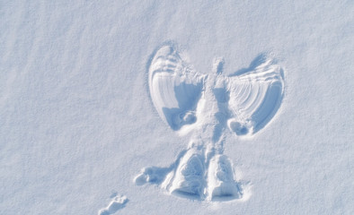 Snow angel's print on a snowcovered area. Aerial foto. Wall mural