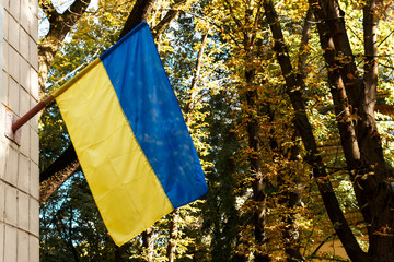 Ukrainian flag hanging on the house. Ukraine blue and yellow banner. National flag of Ukraine waving on a home.