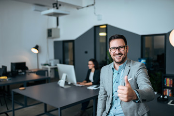 Portrait of a elegant businessman showing thumbs-up at coworking office.