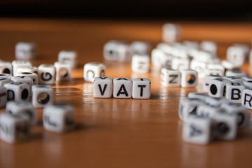 The word VAT made of white plastic blocks on the table. Letter concept.