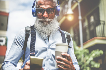 Happy senior man listening music playlist app and drinking coffee at early morning time