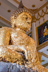 Sitting Buddha gilded of petals inside Buddhist temple in Thailand. Golden foil on Buddha statue.