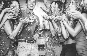 Happy friends having fun throwing confetti at vintage cocktail bar party