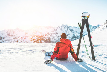Poster Winter sports Skier athlete sitting in alpes mountains on sunny day - Adult man enjoying the sunset with skies gear next to him - Winter sport and vacation concept