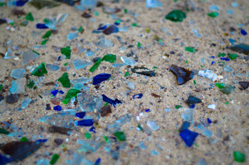 Broken glass bottles on white sand. Bottles is green and blue colour. Trash on the sand. Ecological problem.