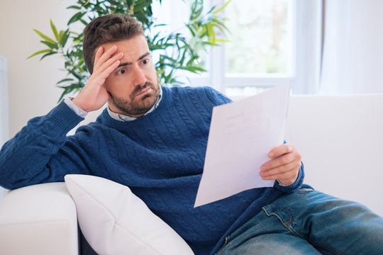 Concerned man reading tax form at home and having bad surprise