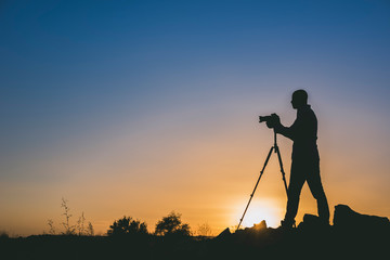 Silhouette of black photographer at sunset