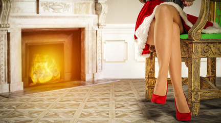 Slim young woman legs with red heels and fireplace background.