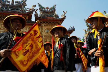 Participants march with the 'Wang Yeh's Boat', a 13-meter finely crafted ancient warship made of paper and wood, which will be burnt during the Wang Yeh Boat Burning Festival in Pingtung