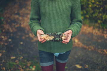 Young owman in nature with lichen covered wood