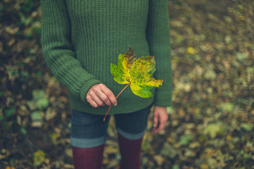 Woman in the woods holding a leaf