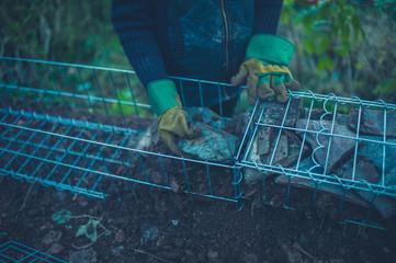 Gardener putting rocks in gabian
