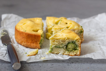 Corn cake with broccoli on parchment paper.