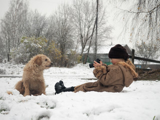 The child takes pictures of the dog. Funny photo shoot of your favorite pet