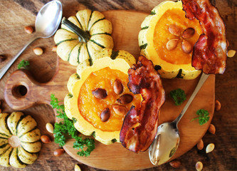 Pumpkin soup with crisp bacon served in a hollowed pumpkins