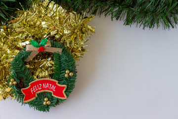 Christmas decorations . Garlands, lights and tinsel.Merry Christmas greeting message written in Portuguese