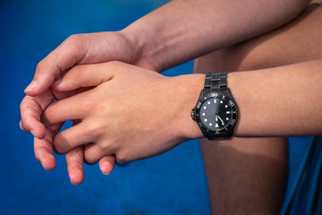 Close up of male hands and arms wearing a black automatic steel wristwatch.