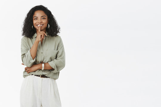 Shh I prepare surprise. Joyful charismatic and stylish african american girlfriend with curly hairstyle shushing at camera and smiling with joyful look telling secret against gray background
