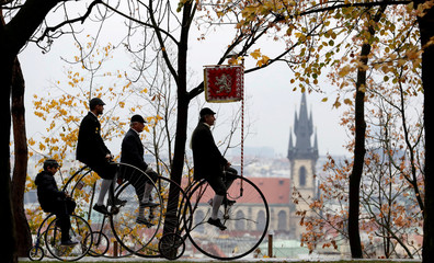 Participants wearing historical costumes ride their high-wheel bicycles during the annual penny farthing race in Prague