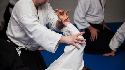 Aikido athletes train in the dojo. Aikidoki work out the elements of aikido equipment