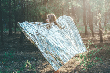 Fototapeta Beautiful girl is wrapped in a foil emergence blanket. Wet model stands in the forest in the morning. Concept of the tourist who studied the problems of pollution of nature who was wet from the water