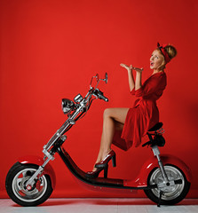 Woman pinup style ride new electric car motorcycle bicycle scooter present for new year 2019 in red dress pointing hands up