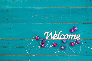 Welcome sign with Christmas ornaments and white ribbon on teal blue wood background; holiday background with copy space