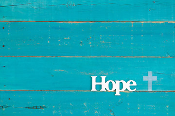 The word Hope and white cross hanging on rustic teal blue wood background; religious background with copy space