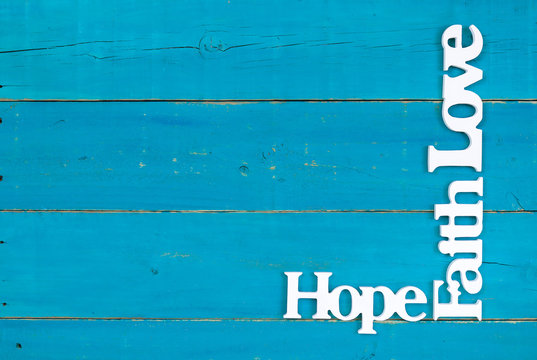 Hope, Faith and Love hanging on rustic teal blue wood background; spiritual background with copy space