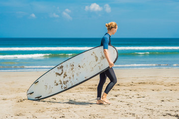 Young woman in swimsuit with surf for beginners ready to surf. Positive emotions