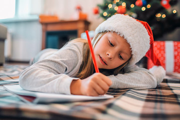 Diligent girl is lying on blenket on floor and writing letter to Santa. She uses red pencil. Girl is serious and concentrated. She is in room alone. There are Christmas tree with presents behind her.
