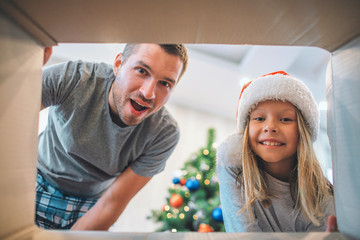 Excited and happy family looking inside of box. Young man wonderes. Girl is smiling. She wears hat. There are Christmas tree behind them.