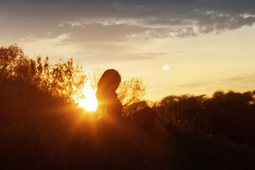 Printed kitchen splashbacks Brown silhouette of a young woman sitting on a hill at sunset, a girl walking in the autumn in the field