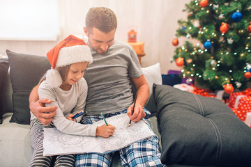 Picture of father and daughter sitting together on sofa. They are drawing. People are serious and concentrated. Young man embraces his daughter. They sit in decorated room with Christmas tree.