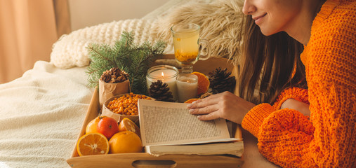 Soft cozy photo of woman in warm orange sweater on the bed with cup of tea and fruit. Girl sitting on the bed with old books.