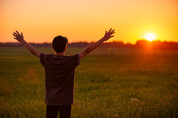 Boy raised his arms in the air with sunset background