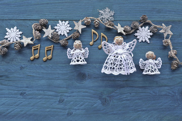 Advent  night with music notes, singing angels on wooden background