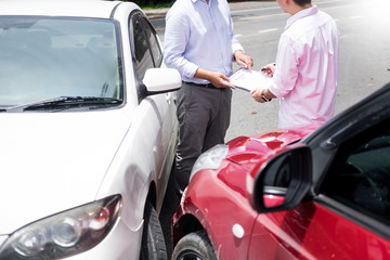Obraz Insurance agent writing on clipboard while examining car after accident claim being assessed and processed. - fototapety do salonu