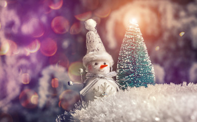 snowman and holiday clock of snow at new year night with a colored lights