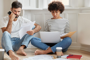 Photo of two mixed race coworkers read documentation, concentrated on solving problem with planning, check email box on laptop computer, drink coffee, look through delivered bills, sit on floor
