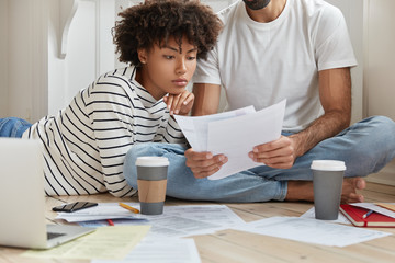 Hard working interracial marketing experts pose on floor, study documentation, make monthly report, share opinions about startup, lie on floor, watch training video on laptop, drink takeaway coffee