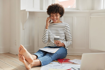 Glad black woman with Afro haircut, talks via cell phone while reviews documents, uses laptop computer during coffee time, wears striped sweater and jeans, has bare feet, sits on floor in empty room