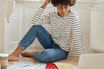 Photo of dark skinned woman checks paper graphics during remote job, plans budget income, checks bills, uses electronic device for studying, sits barefoot on floor, dressed in casual clothes