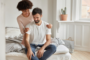 Happy young African American woman shows positive pregnancy test to her husbnad, rejoice good news of becoming parents soon, pose on unmade bed in spacious cozy bedroom. Planning family concept