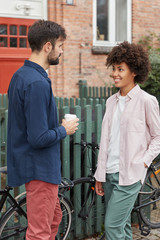 Vertical shot of interracial woman and man stand opposite each other, drink takeaway coffee, speak about something, pose near bikes and fence in rural area. People, communication and lifestyle