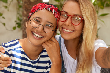 Close up shot of mixed race friendly two girls pose for selfie, demonstrate interracial friendship, embrace each other, wear spectacles, smile broadly at camera, spend leisure time together.