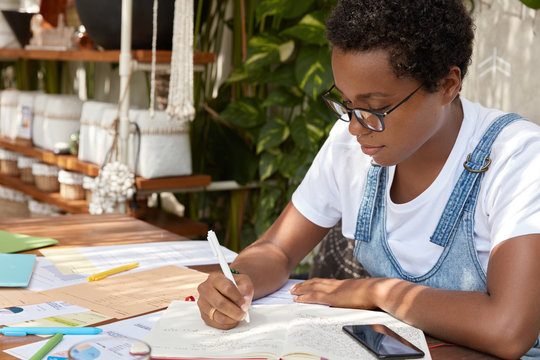 Sideways shot of dark skinned lady in casual clothes, writes down in notebook, checks paper graphics, works freelance, wears optical glasses, edits text on free time. People and work concept