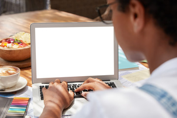 Unrecognizable dark skinned woman keyboards on laptop computer with blank screen area for advertising content, checks database, makes online research, does written tasks, sits at coworking space