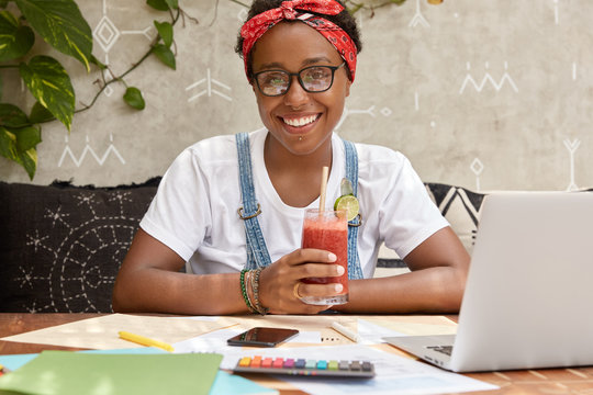 Positive female tourism worker develops website of travelling agency, studies financial side, drinks fresh beverage, wears casual t shirt, spctacles and red bandana, models in cozy interior alone