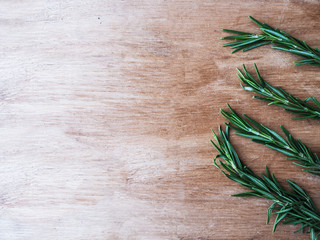 Top view of fresh rosemary herb lined up horizontally on a brown wooden cutting board with copy space on the left.